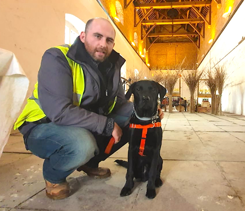 Archaeologist James Miles squats next to a sitting black labrador puppy wearing a bright orange harness inside an old building with a high ceilling, wooden rafters, and stone paving.