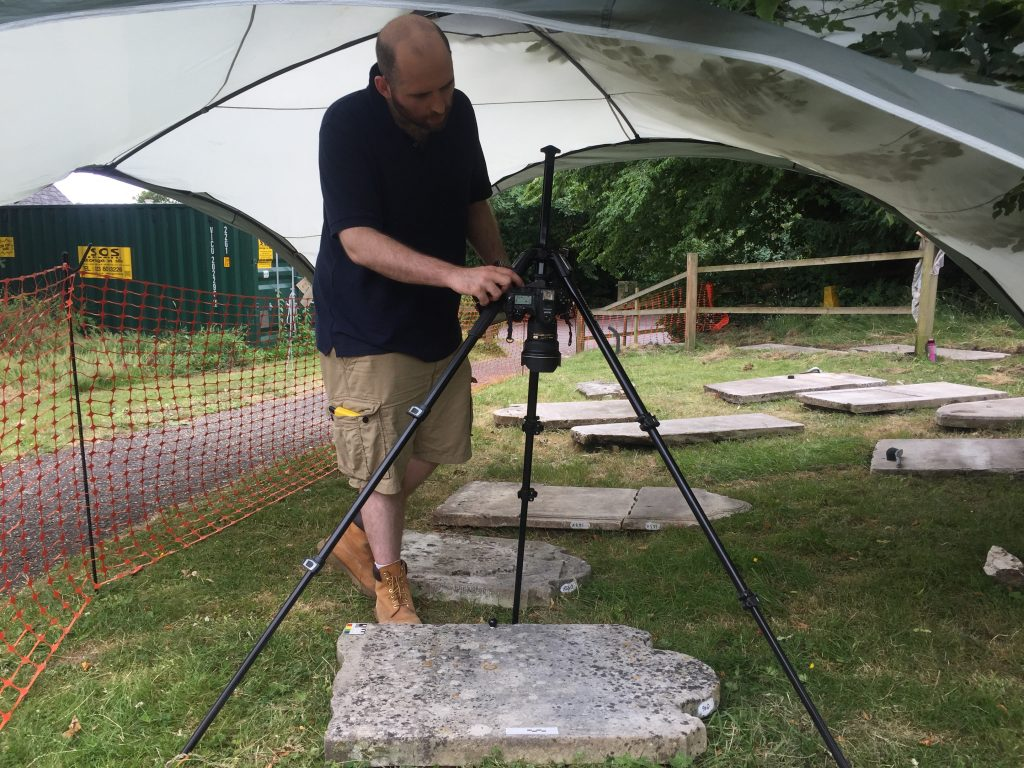 A man stands under a gazebo in the churchyard, operating camera on a tripod pointed directly down to photograph a headstone laid flat on the ground. There is a photographic key on the headstone and small black ball, and in his hand he holds a handheld camera flash.