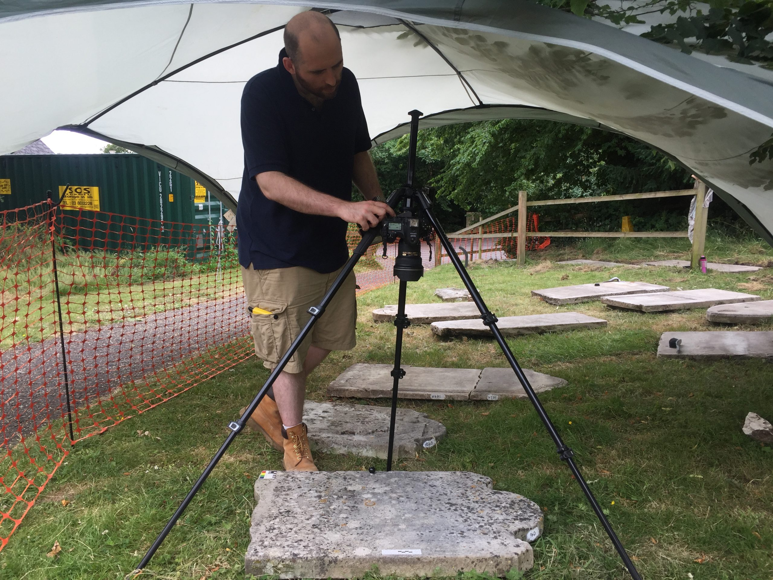 A man stands under a gazebo in the churchyard, operating camera on a tripod pointed directly down to photograph a headstone laid flat on the ground.