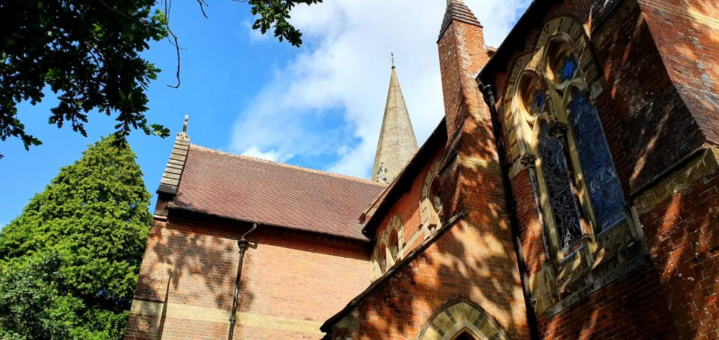 A view upwards of the windows and roof of a red brick church with a tall spire surrounded by trees.