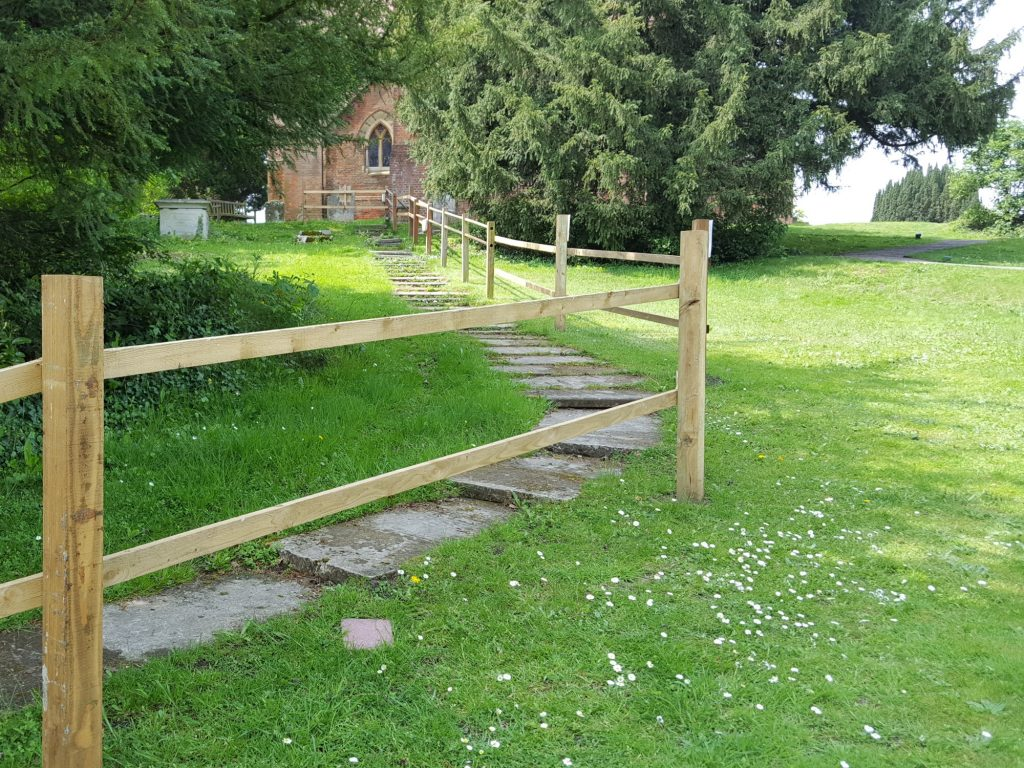 View of headstones laid flat as steps to make a path down a grassy green hillside from a red brick church. The path is fenced off from use by a wooden fence.