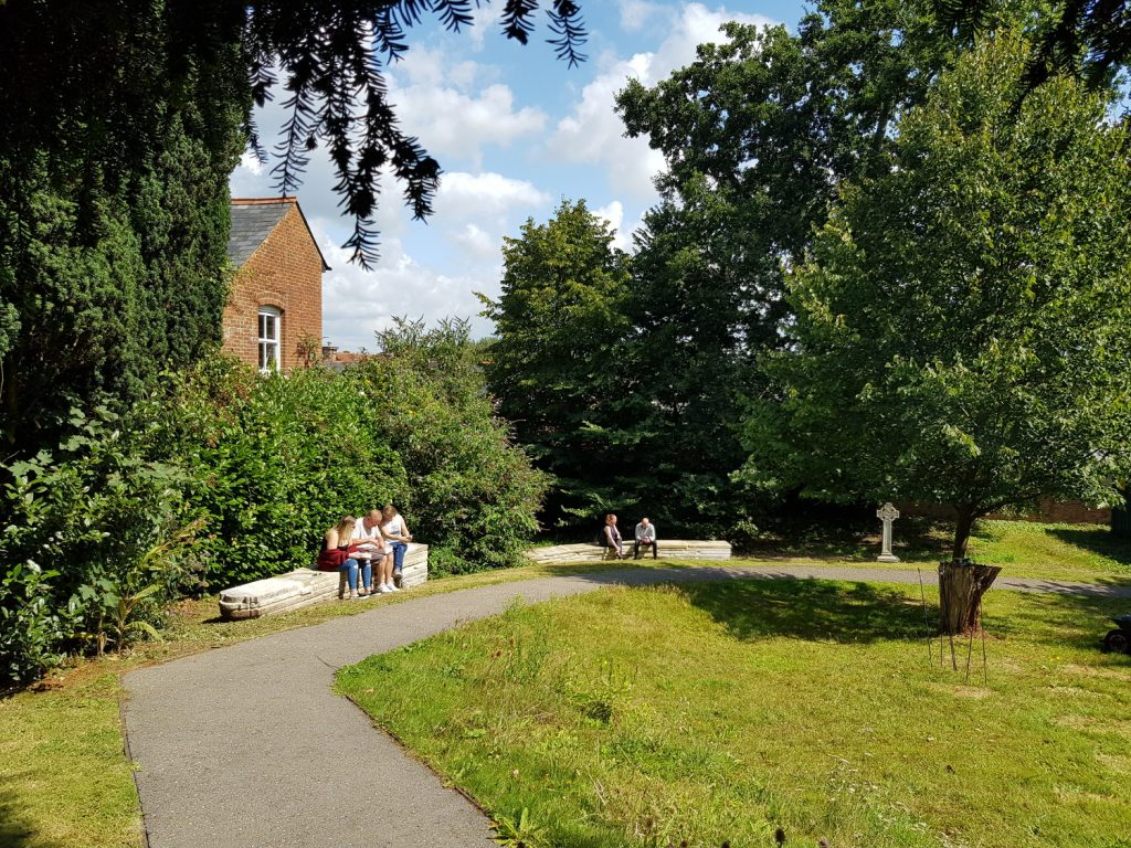 A view of the churchyrad after the project ended: the path is now made of tarmac and the headstones have been laid on top of and beside each other to form two long benches which people are sitting on.