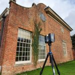 A laser scanner stands on a tripod outside an old redbrick building and manicured garden.